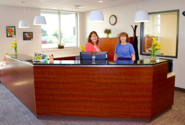 2 business office staff standing behind desk
