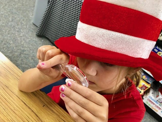 Little Girl in red and white hat with a magnifying glass